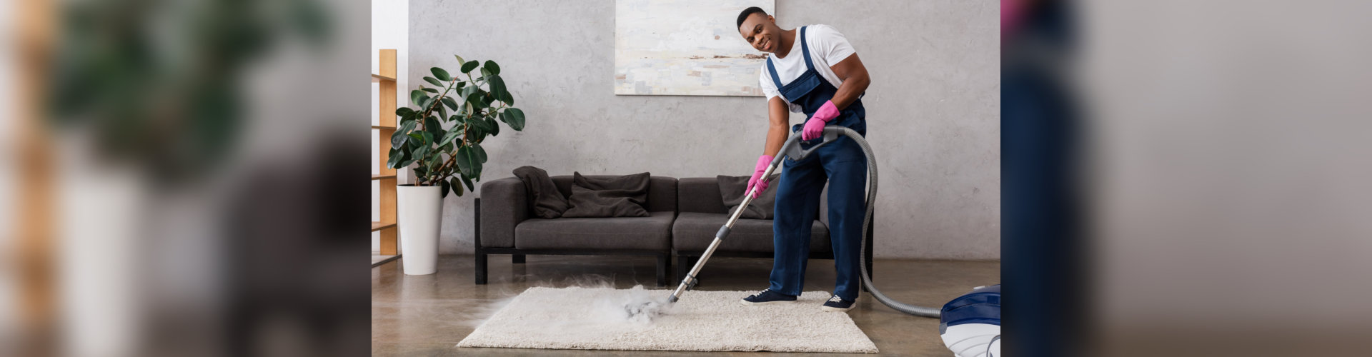 Smiling african american cleaner in overalls using vacuum cleaner with hot steam at home